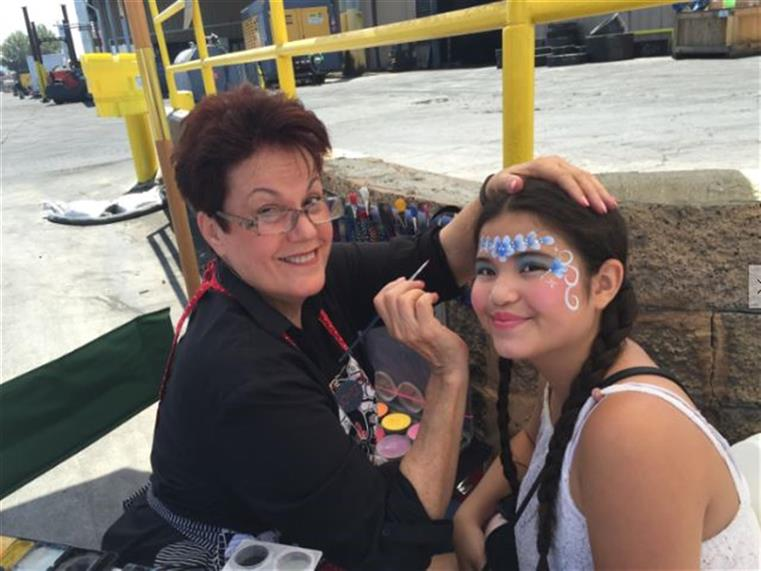 Girl getting her face painted by artist