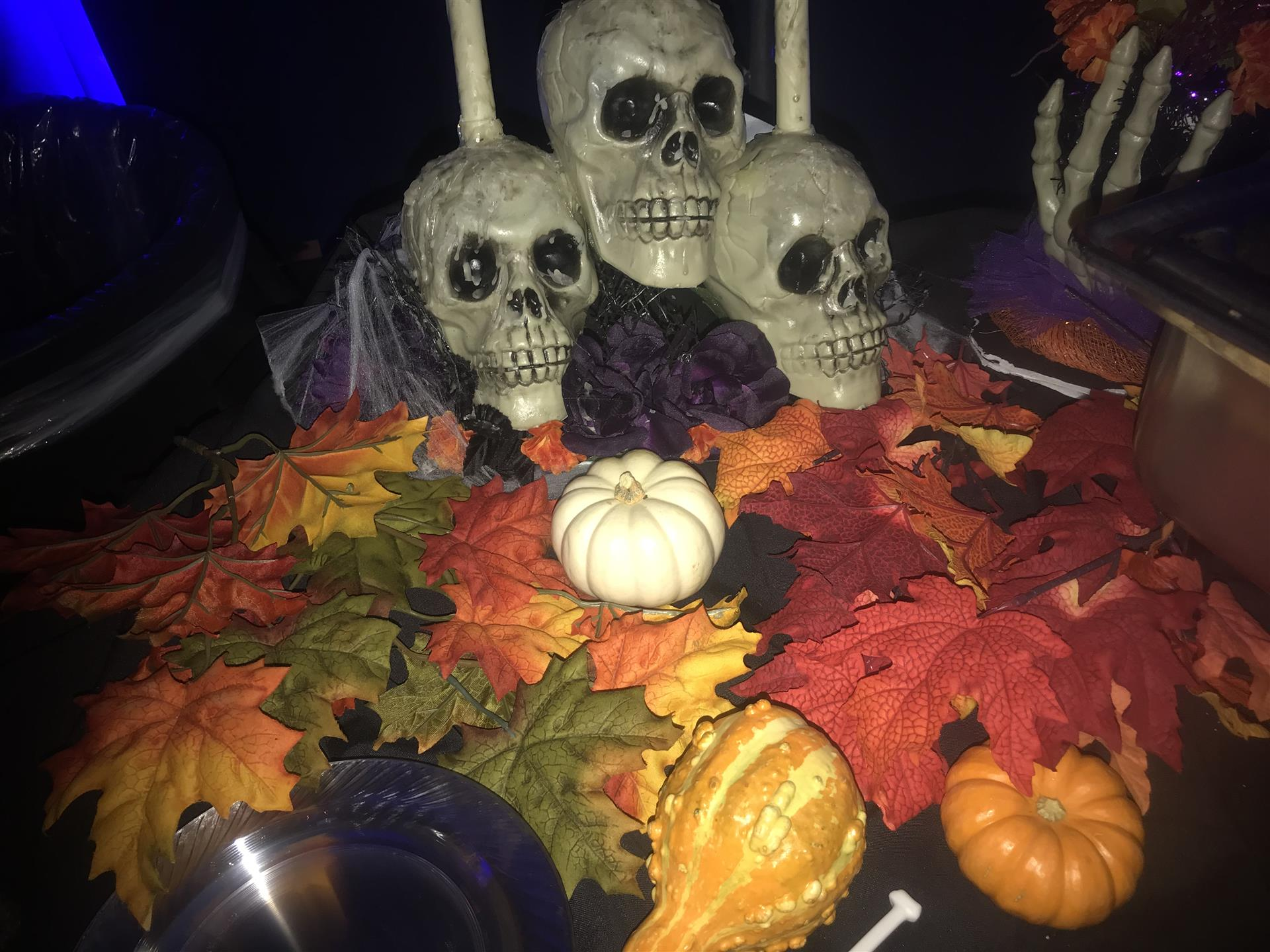 Halloween decor with skeltons, leaves, and pumpkins on a black tablecloth
