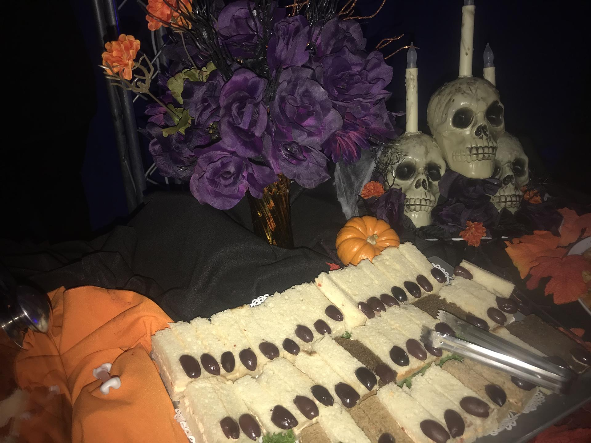 Halloween decorared finger sandwiches on a black and orange table cloth