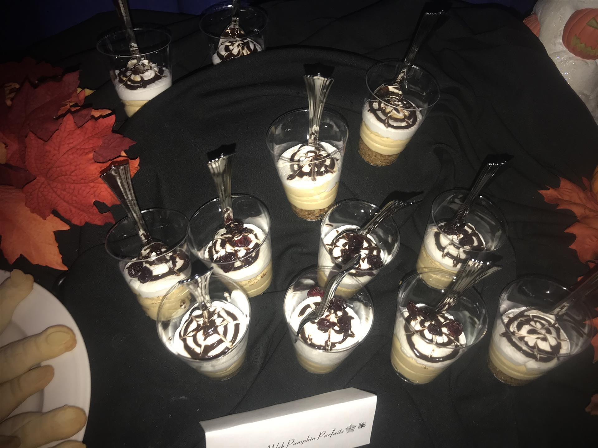 Halloween decorated parfaits with spider web designs on a black table cloth