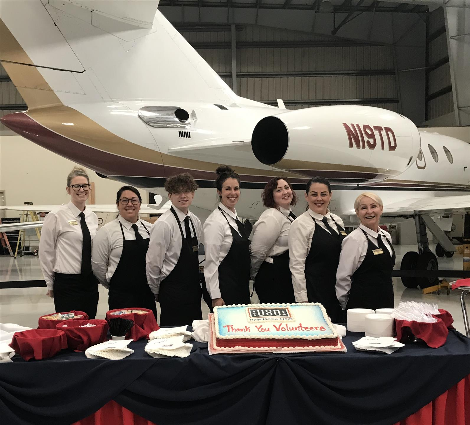 a group of people smiling at the camera behind a cake