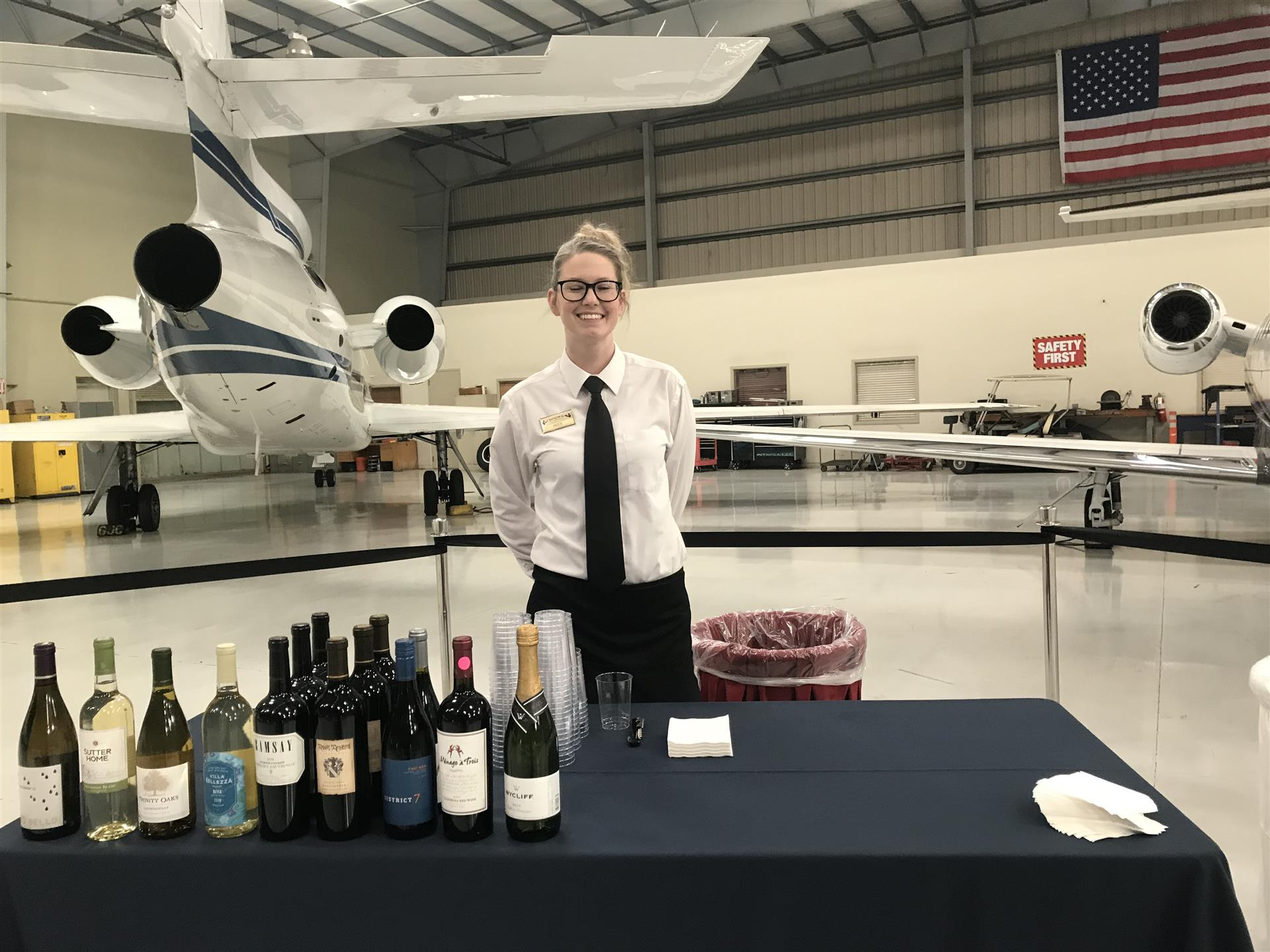 a lady smiling at the camera while sampling wine