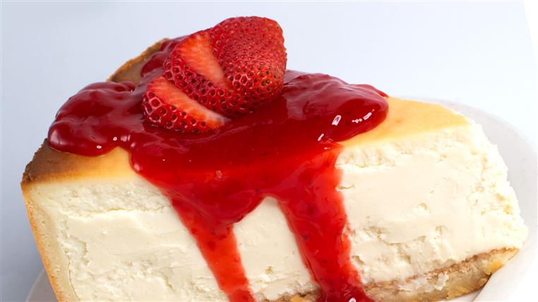 Slice of cheesecake topped with strawberries
