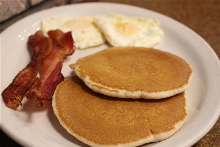 tow pancakes with bacon and two eggs cooked over-easy