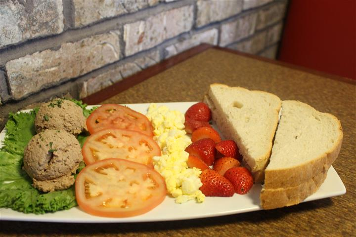 plate with scrambled eggs, fresh strawberries, sliced tomatoes and toast