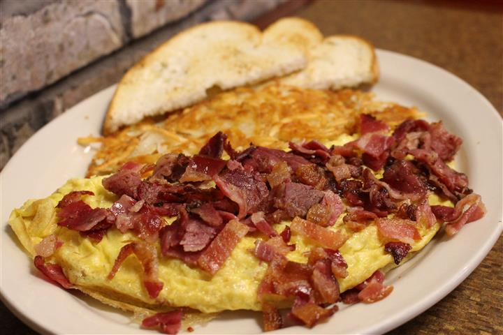 omelette topped with bacon. hashbrowns and toast on the side