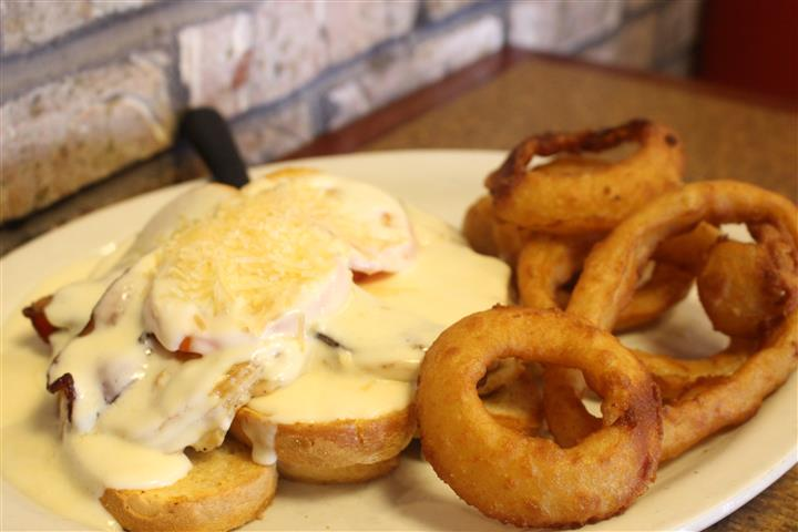 sandwich topped with melted cheese and onion rings
