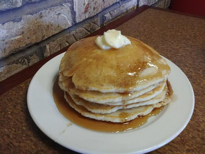 stack of pancakes topped with butter and maple syrup