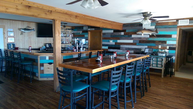 Interior of restaurant - wood tables with tall blue stools. Bar area in corner.