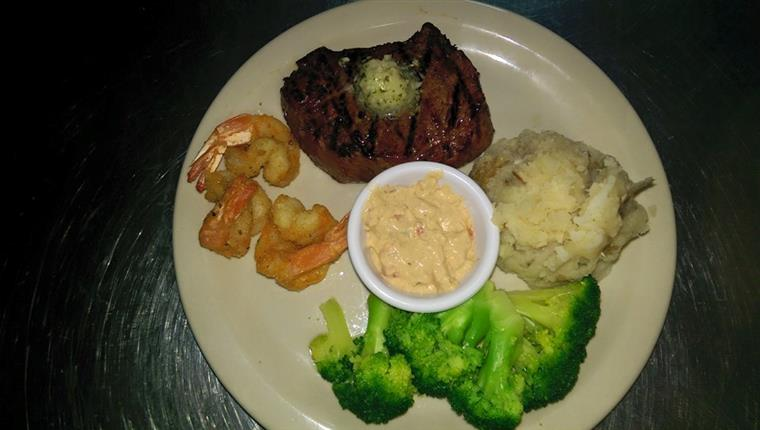 Steak with shrimp, broccoli, mashed potatoes on white dish.