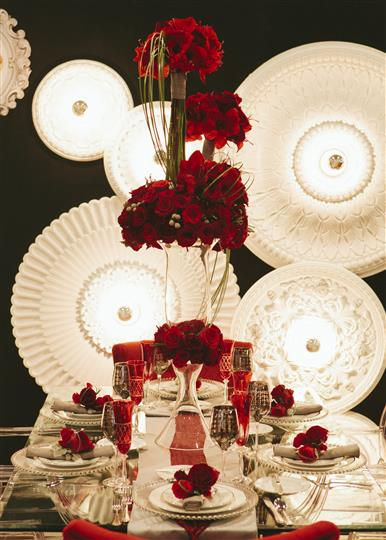 place setting of white napkins, red roses and red rose centerpieces
