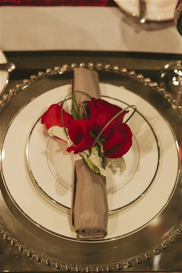 white plate with brown napkin with utensils rolled up with red roses on top