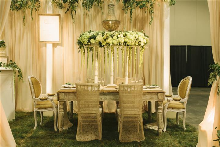 the white table with six chairs around with white floral centerpiece with vines hanging