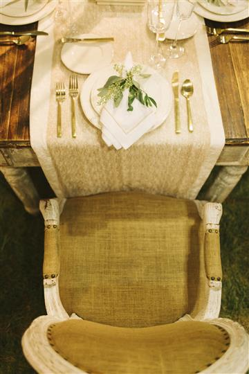 closeup of gold chair with place setting with leaves on top of napkin