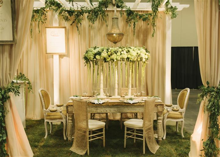 white trellis with vines hanging above a table with a white floral centerpiece with more vines