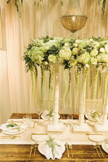 a white table with white floral centerpiece with green vines hanging