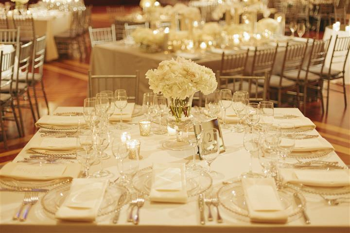 white table with place settings and a rose centerpiece