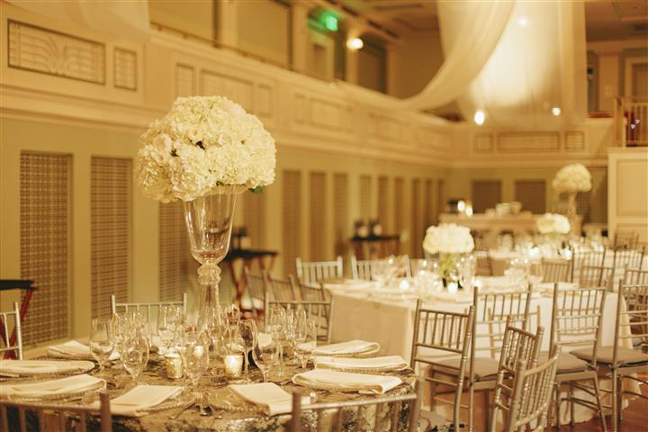 a closeup of the white rose centerpiece on a table with many chairs