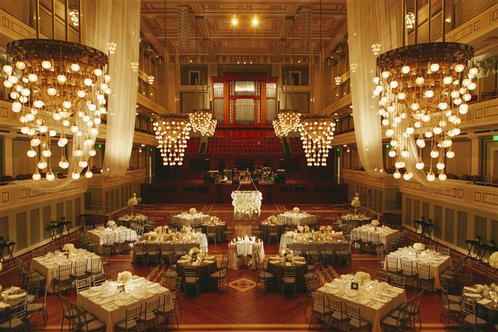 overview of catering room with chandeliers, red wood floors, large white tables