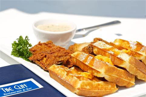 Fried chicken and waffles served with a side of sauce