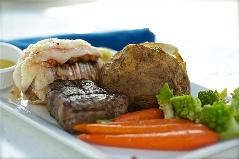 Seafood and steak dish with baked potato and steamed vegetables