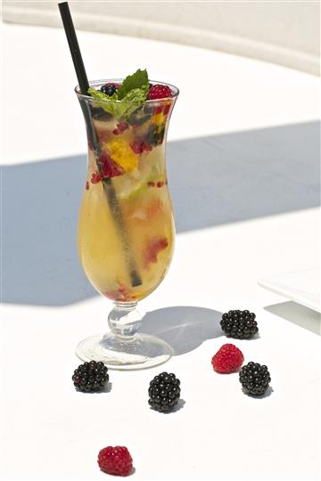 Cocktail with berries and a mint leaf