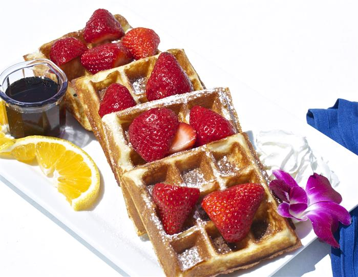 Waffles with strawberries dusted with powdered sugar with a side of syrup