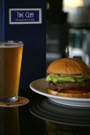 Hamburger with lettuce and tomato served with a pint of beer