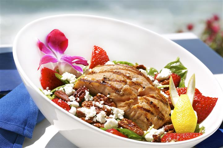 Bowl of salad topped with grilled chicken, decorated with a flower