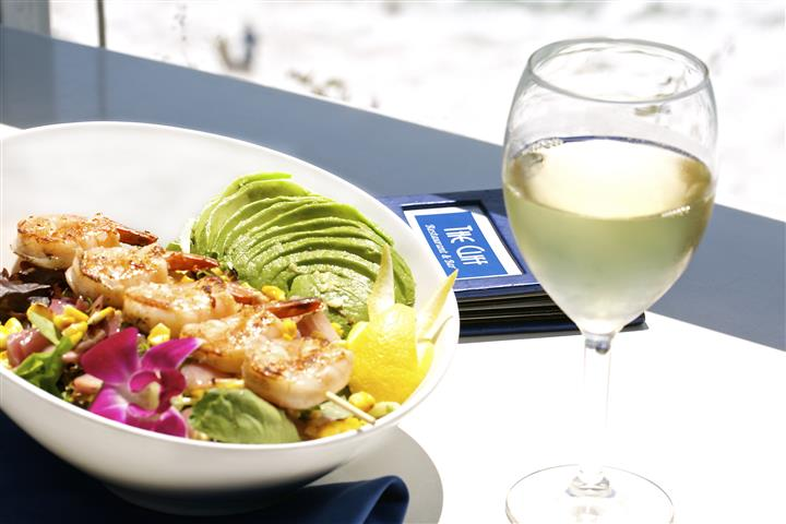 Skewered shrimp with sliced avocado and salad next to a glass of white wine