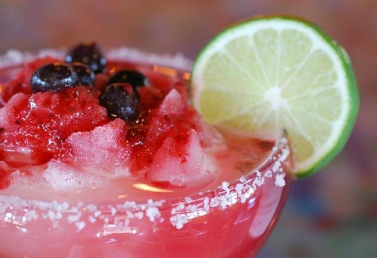 Mixed berry margarita on the rocks with salted rim and a lime slice