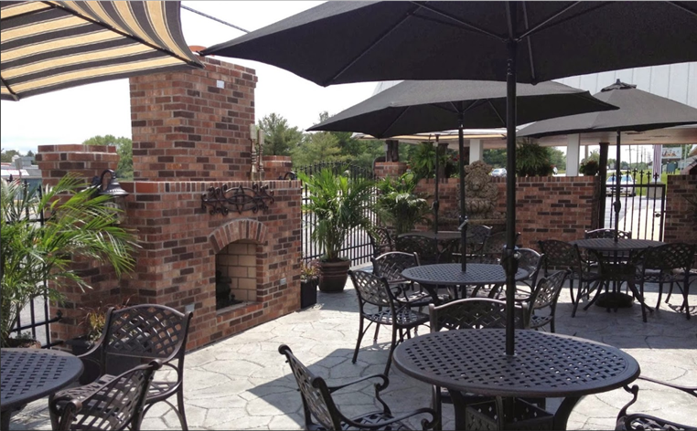 Outdoor seating showing brick fireplace, tables and chairs.