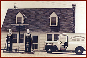 Old black and white image of white truck, house, gas pumps