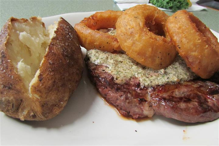 steak with onion rings and a baked potato