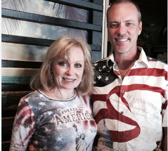 Man and woman wearing american themed clothing posing for photo