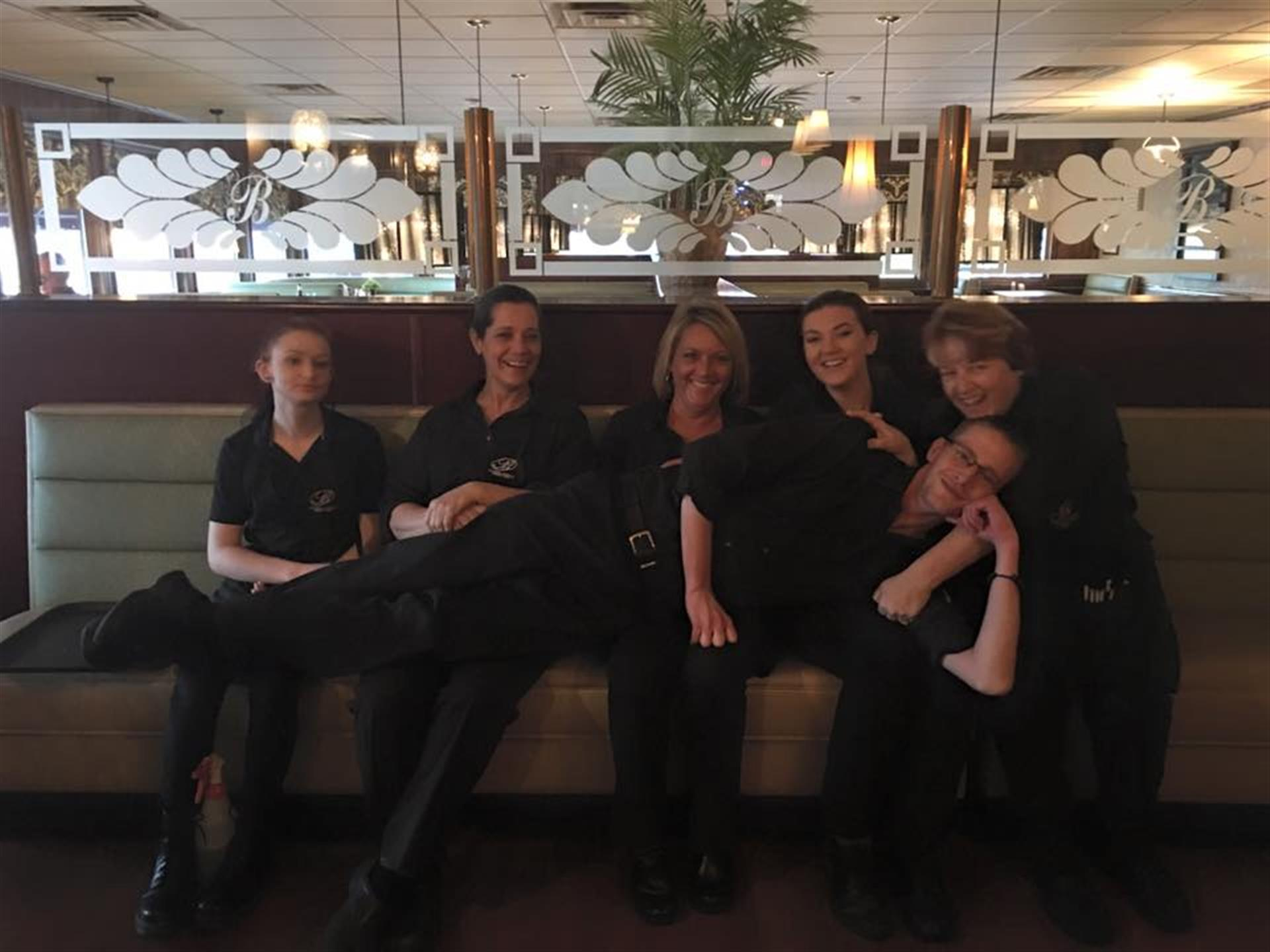 Wait staff posing for photo on waiting bench