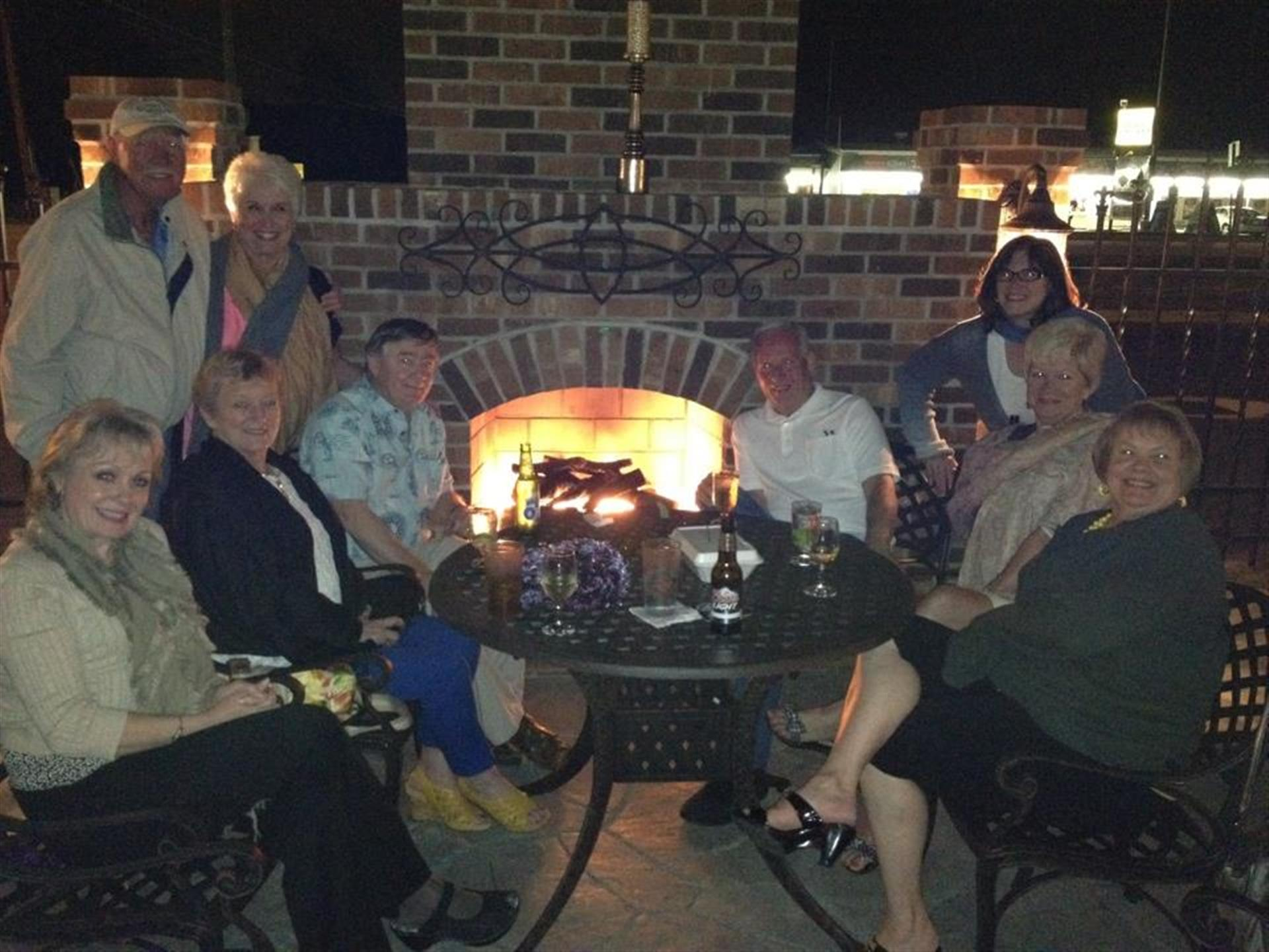Adults gathering around outdoor table in front of fireplace