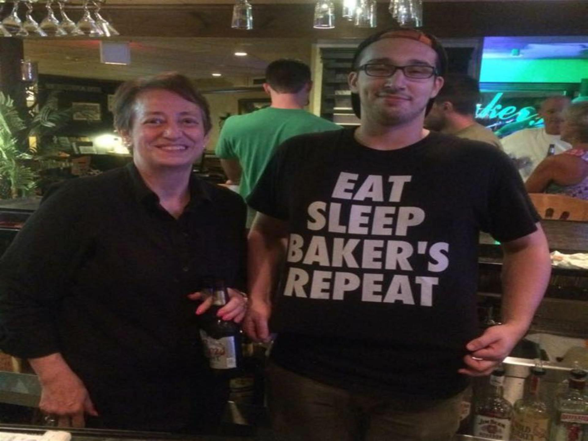 Woman and man Employees behind bar.  Man wearing tee shirt reading Eat, sleep, bakers, repeat.