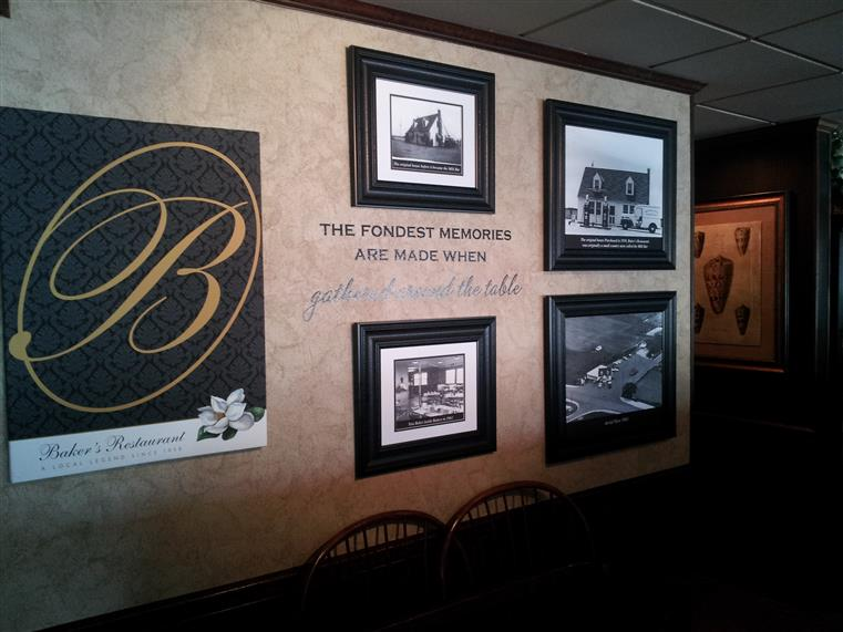 "Wall in baker's restaurant with hanging photographs and words written ""The fondest memories are made when gathered around the table"""