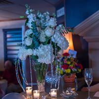 a table centerpiece with flowers and candles