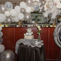 a table with a cake and balloons