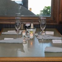 table set up with glasses, napkins, candles, and nametags