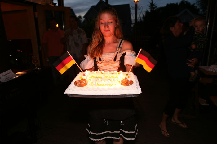 girl bringing out cake with german flags on it