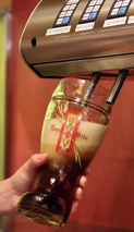 Person filling beer glass from tap system.