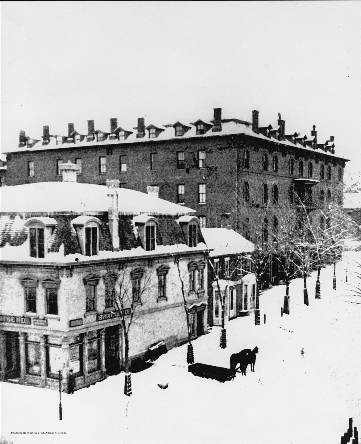 a black and white picture of twiggs building covered in snow