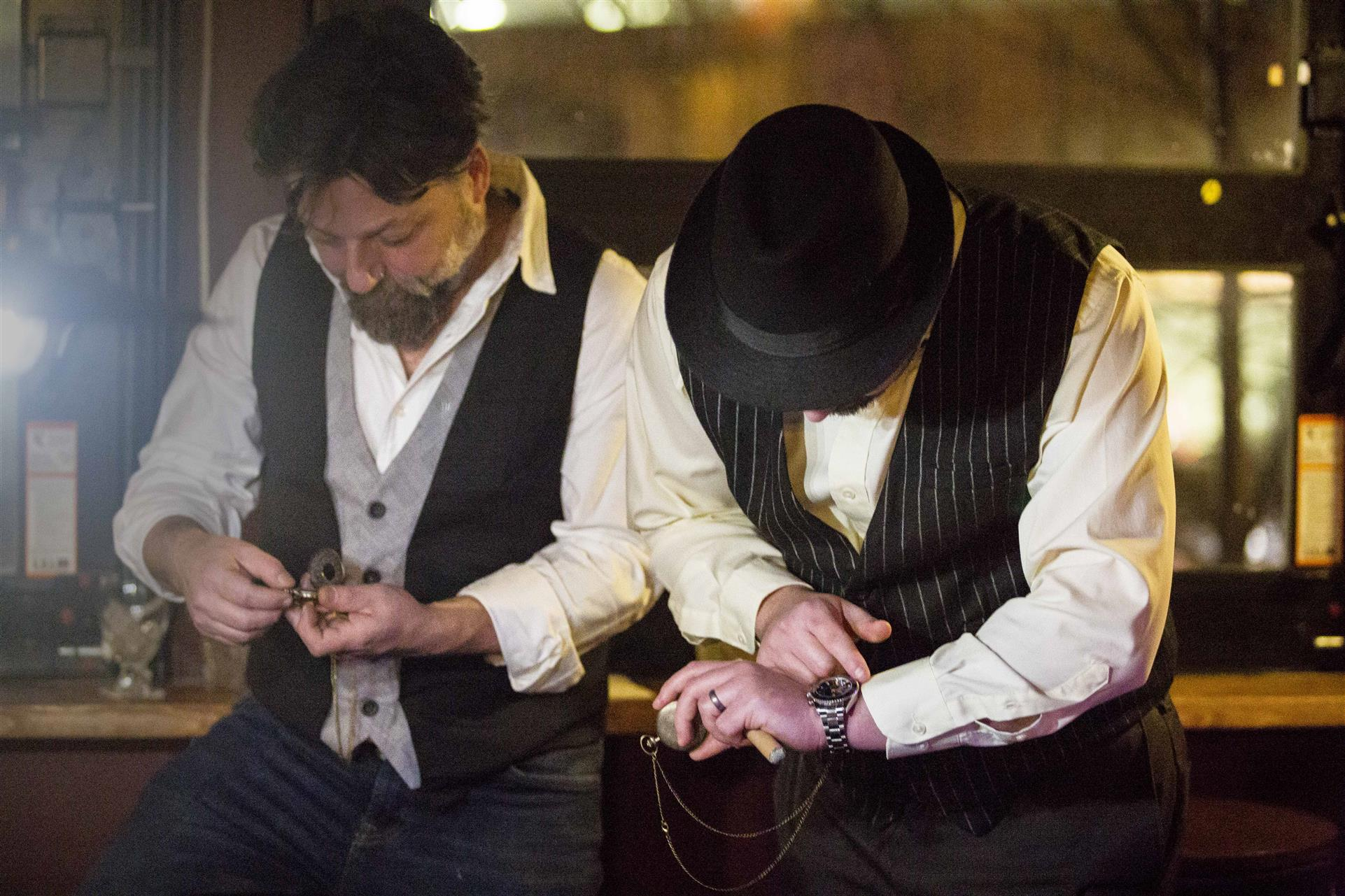 two men dressed in 1920s era checking their watches
