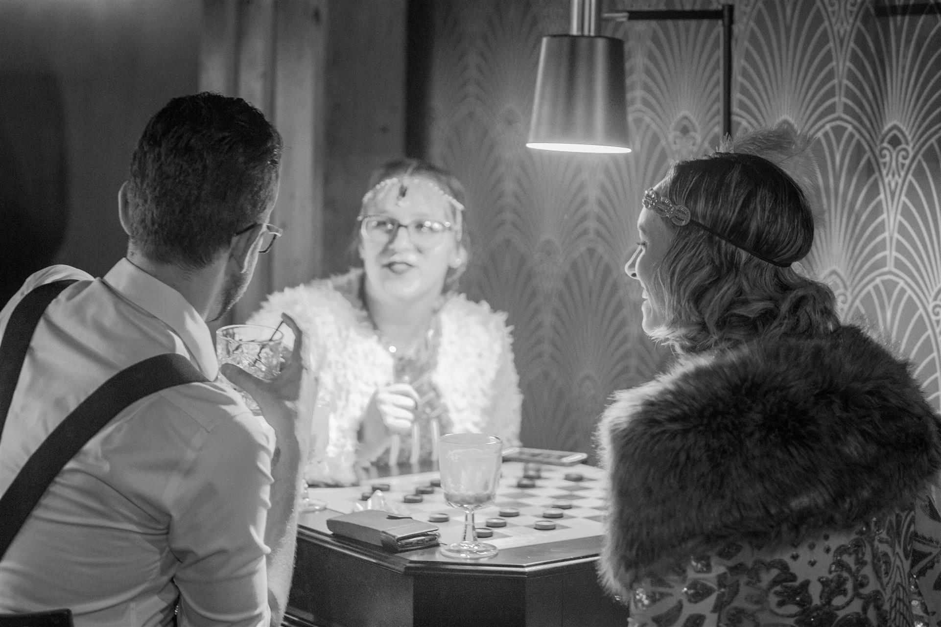 Two men and a woman playing checkers in 1920s era clothing