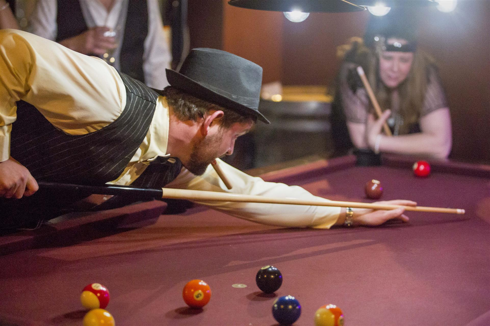 man dressed in 1920s era playing pool