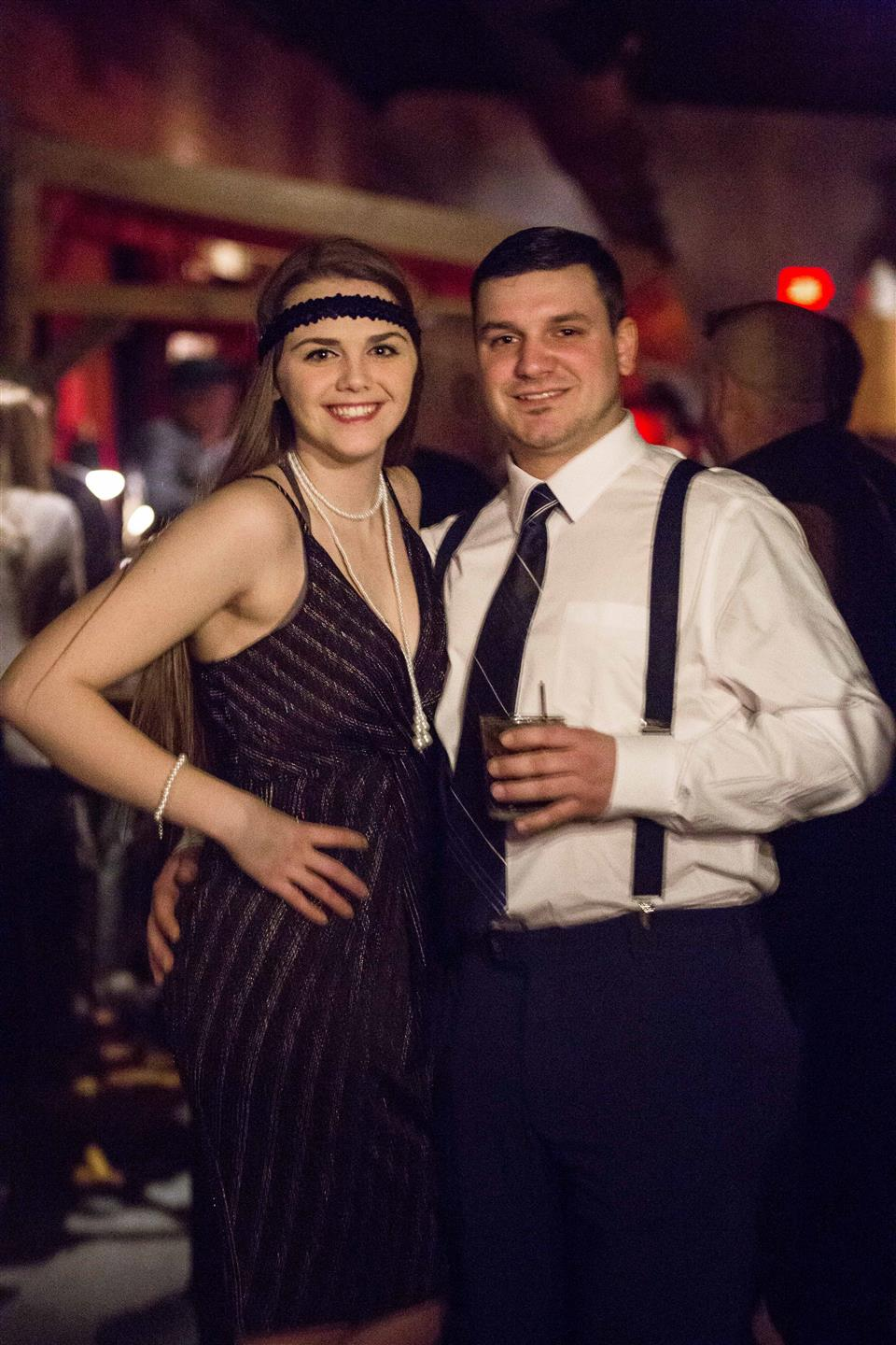 Couple dressed in flapper outfits posing for a picture