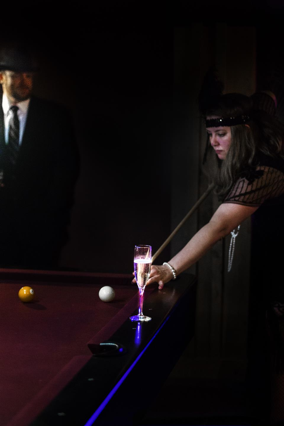 woman in a flapper outfit playing pool with a glass of champagne